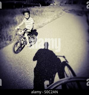 A seven year old boy rides his bike by a man on a bike path. - Stock Photo