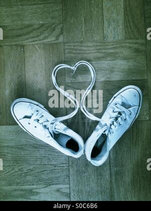 Heart shape in laces with white trainers on a wooden floor. - Stock Photo