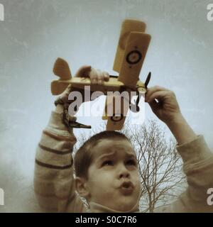 Young boy playing with model biplane - Stock Photo