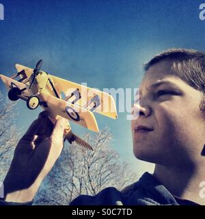 Boy flying his model biplane - Stock Photo