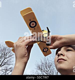 Boy holding his model biplane against the Sky - Stock Photo