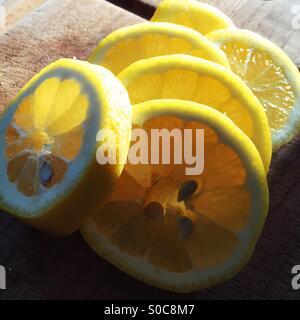 Freshly Sliced Lemon on a cutting board, with raking light illuminating the slices - Stock Photo