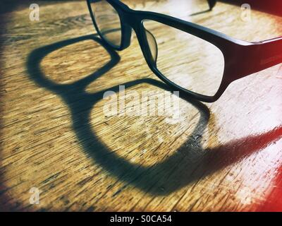A pair of thick rimmed reading glasses sitting on a wooden desk casting a shadow in sunlight. - Stock Photo