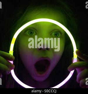 Girl making funny face looking through glow stick necklace in the dark - Stock Photo