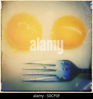 Two broken egg yolks and a fork. Faces in objects - Stock Photo