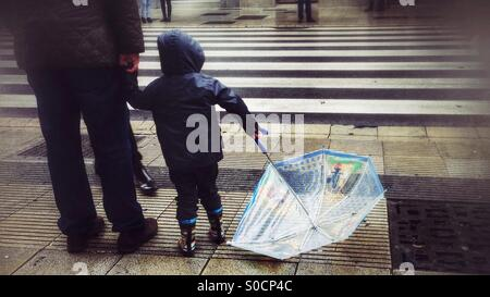 Boy with umbrella waiting at a road crossing - Stock Photo
