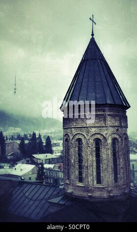 Georgian Orthodox Church Tower with crucifix on domed roof. In background through the mist of an overcast day The - Stock Photo