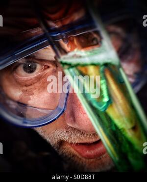 Scientist inspecting reaction in test tube - Stock Photo