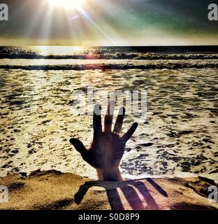 Help! Hand Reaching Up From The Water Into The Light - Stock Photo
