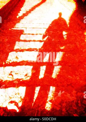 Shadow of man walking down stairs - Stock Photo