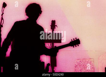 Glowing silhouette of Tim Carter of Kasabian at Brixton Academy 4th December 2014. - Stock Photo