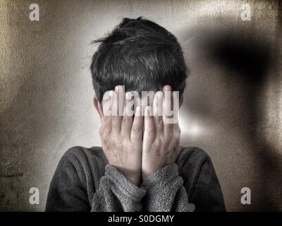 Boy hiding face with hands - Stock Photo