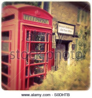 Old style red telephone kiosk, not in use, in the garden of Weston Underwood Old Post Office. - Stock Photo
