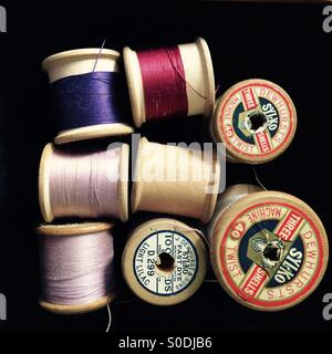 Old wooden cotton reels with coloured thread. - Stock Photo