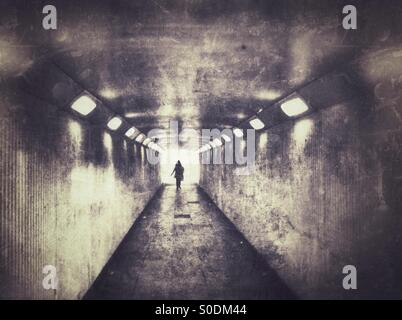 Lone female walking in dark underpass. - Stock Photo