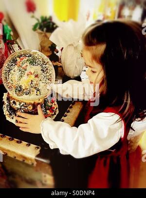 Little girl looking into a snow globe on Christmas morning - Stock Photo