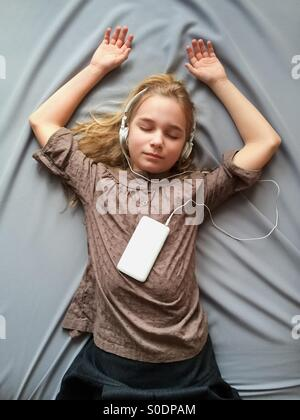 It sounds like a dream. Young girl lying on the bed and dreaming about something with closed eyes - Stock Photo
