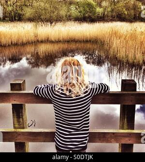 Young girl looking out over pond at Yarrow Valley near Chorley in Lancashire - Stock Photo