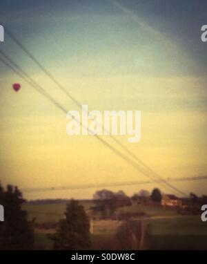 A hot-air balloon seen from a train window - Stock Photo