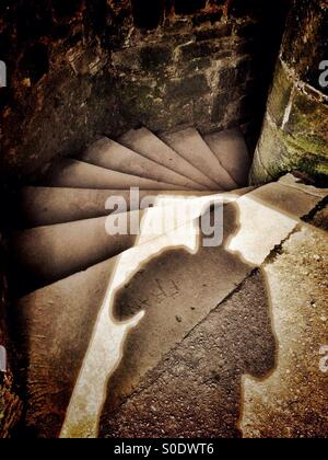 Mysterious shadow at top of stone spiral staircase (Darwen Tower, Blackburn) - Stock Photo