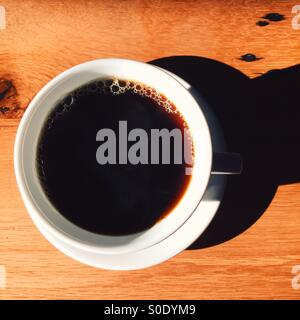 And overhead shot of a fresh cup of coffee on a wooden table. White cup and saucer, simple composition with dark - Stock Photo