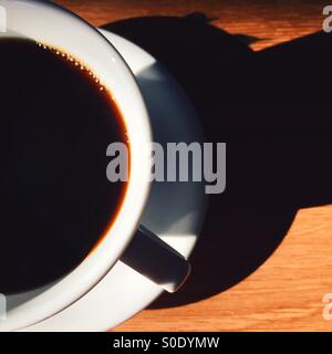 And overhead close-up shot of a fresh cup of coffee on a wooden table. White cup and saucer, simple composition - Stock Photo