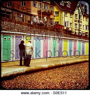 Row of brightly painted beach huts, with a man and woman walking in front; Lyme Regis, Dorset. - Stock Photo