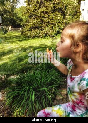 A girl in a floral dress sits on a patio blowing bubbles (1). - Stock Photo