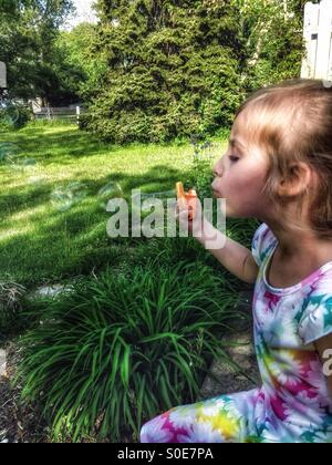A girl in a floral dress sits on a patio blowing bubbles (2). - Stock Photo