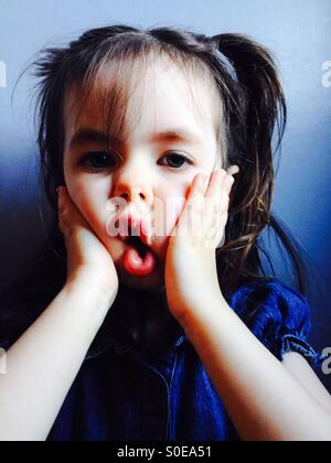 3-year old girl making funny face - Stock Photo