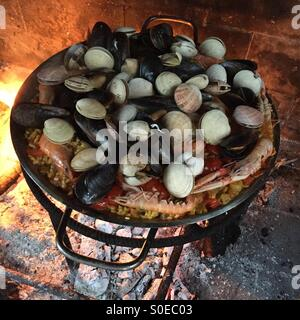 Seafood paella cooking on an open fire in Vacarisses, Catalonia, Spain. - Stock Photo