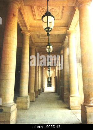 Beautiful classical columns and antique pendant ceiling lamps line the arcade of Valois Gallery at Palais-Royal. - Stock Photo