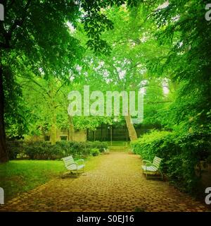Verdant green Parc de Bercy with stone pavement, benches, trees and fresh Spring foliage in Paris, France. Vintage - Stock Photo