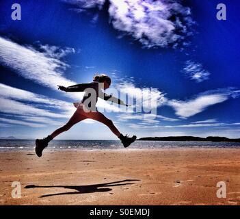 Leap for joy on Newborough beach, Anglesey - Stock Photo
