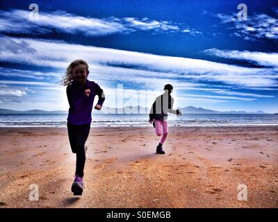 Two young girls running on Newborough beach on Anglesey in North Wales - Stock Photo