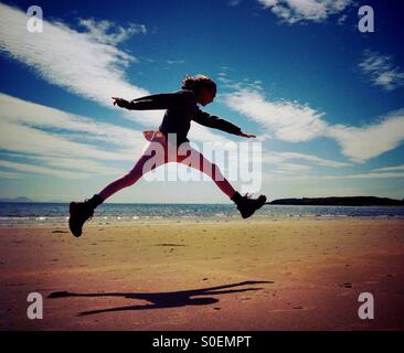 Young girl leaping for joy on Newborough beach on Anglesey - Stock Photo