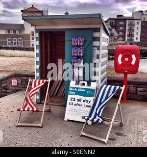 Deck chairs on a grey, windy bank holiday Monday in Weston-super-Mare - Stock Photo