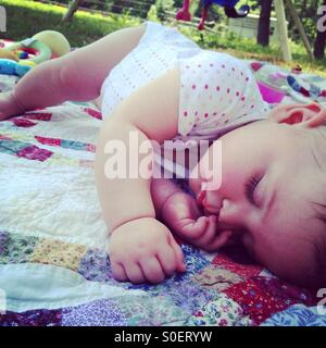 Sleeping baby napping outside on a quilt - Stock Photo
