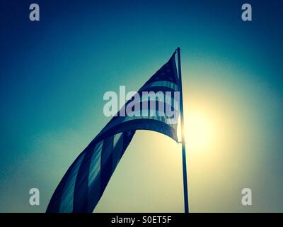 American flag outside on a flagpole with the morning sun behind it - Stock Photo