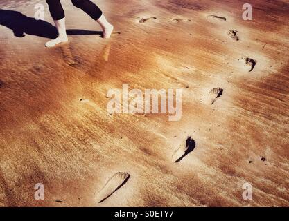 Footprints curving round in sand at beach - Stock Photo