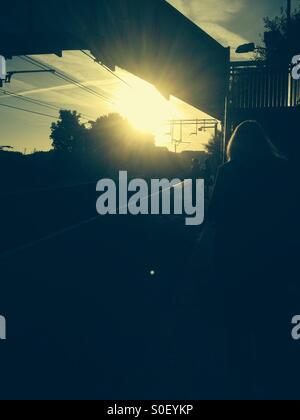 Early morning commuters waiting for the train - Stock Photo