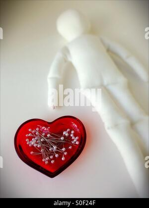 Pins in a heart shaped dish next to a blank voodoo doll. - Stock Photo