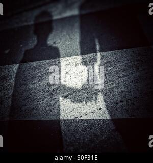 Shadow of an adult holding a hand of a kid over a zebra crossing - Stock Photo
