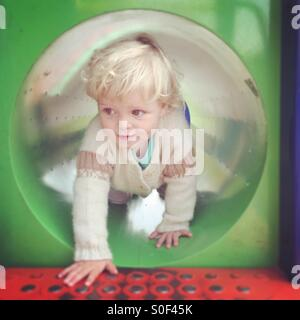 Little girl emerging from a tunnel in climbing frame - Stock Photo