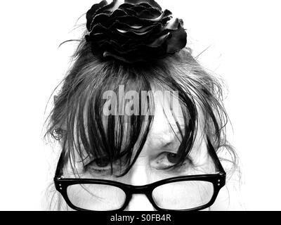 Old age pensioner wearing reading glasses and flower in her hair - Stock Photo