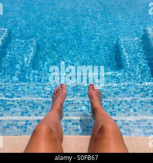 Feet and legs on a swimming pool with a square shape of steps - Stock Photo