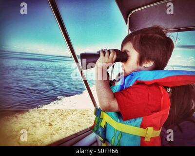 A little boy on a boat ride wearing a life jacket looks out to sea using a pair of binoculars. - Stock Photo