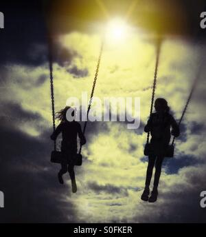 Two girls on swings in silhouette against evening sun - Stock Photo