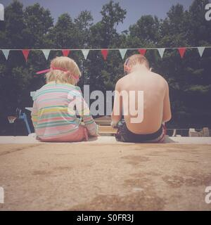 Two young children sitting next to each other on the side of a swimming pool. - Stock Photo