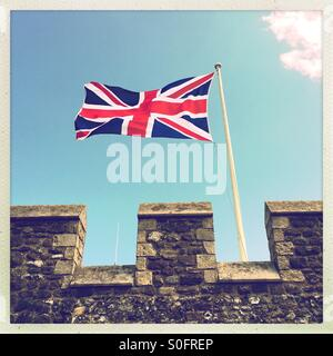 A Union Jack flag blowing in the wind. - Stock Photo
